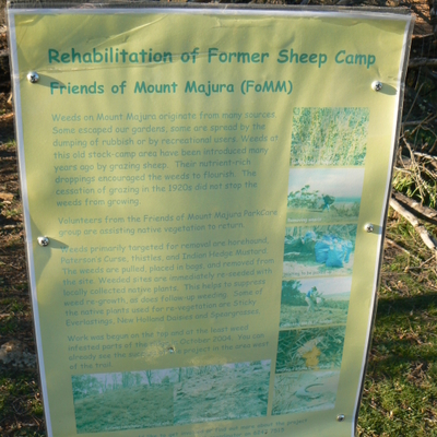 A sign at the path intersection promoting the preservation of Mount Majura. The sign is quite faded, which indicates it has been there a while.