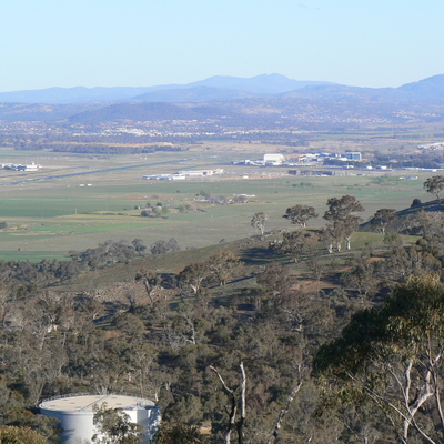Canberra Airport in the distance, and a water reservoir on the mountain.