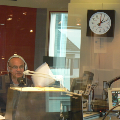 John Stanley waving papers around while he talks.  I like the clock in the background, especially the red numbers which continue the 24 hour clock beyond the midday.